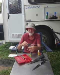 Phil the happy camper outside his campervan, sharpening knives
