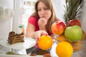 woman hesitating as she chooses fruit over chocolate cake