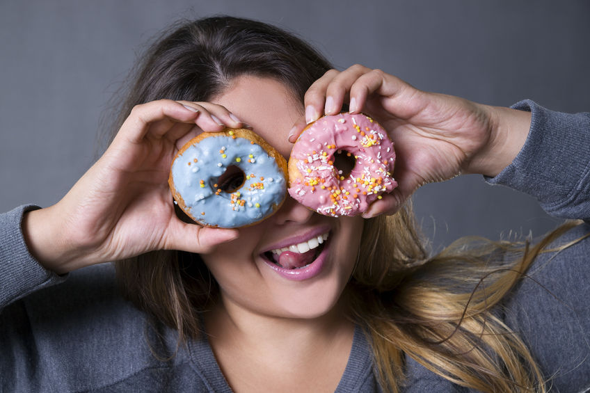 young woman holds iced doughnuts up like spectacles