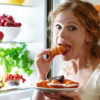 woman with guilty look eating from open fridge with plate of goodies in hand